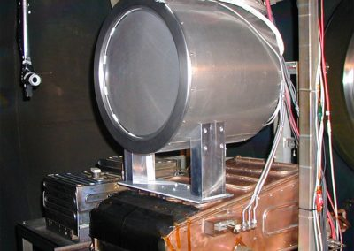 LM4 engine mounted on PEPL thrust stand. A vacuum rated camera mounted on a rotational theta table (shown to the left of the engine) allowed visual monitoring of the discharge cathode during ignition and provided flexibility in diagnosing any operating problems.